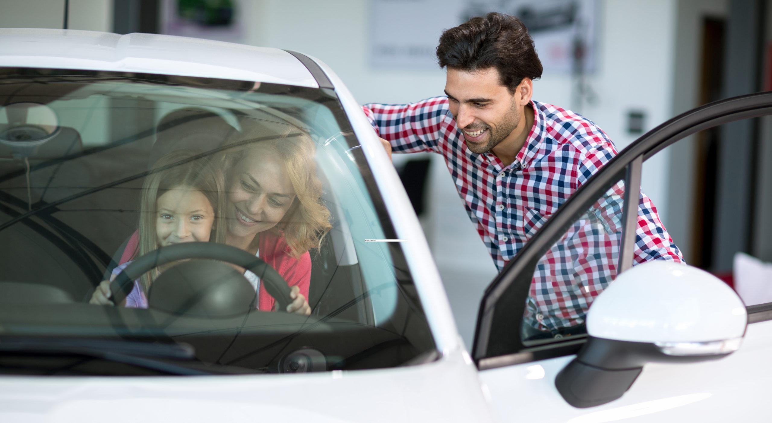 car salesman handshaking with cheerful buyer